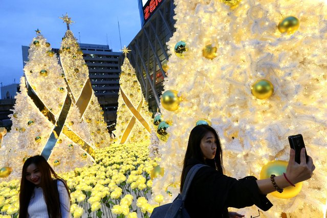 Women pose for photos near Christmas decorations to celebrate the upcoming Christmas season, in front of a department store in the shopping district of central Bangkok, Thailand, December 15, 2016. (Photo by Athit Perawongmetha/Reuters)