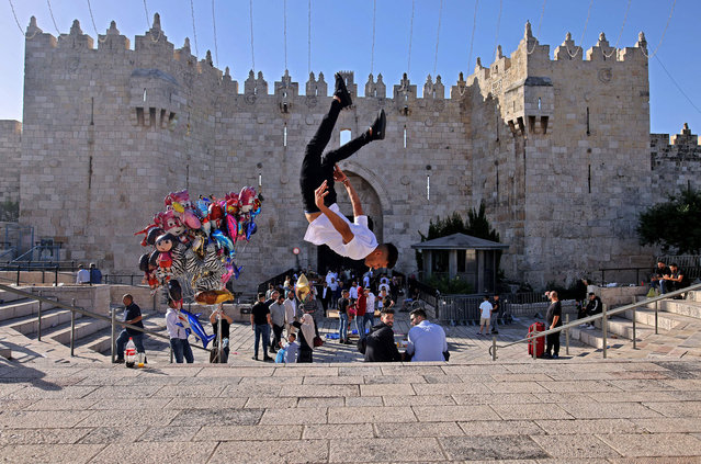 A Palestinian youth performs a jump outside the Damascus Gate in Jerusalem's Old City on May 13, 2021 during Eid al-Fitr, which marks the end of the holy fasting month of Ramadan. (Photo by Ahmad Gharabli/AFP Photo)