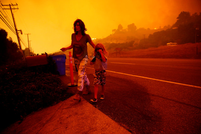 Gabi and Jonah Frank walk on Pacific Coast Highway as the Woolsey Fire threatens their home in Malibu, California, U.S. November 9, 2018. The fire destroyed dozens of structures, forced thousands of evacuations and closed a major freeway. (Photo by Eric Thayer/Reuters)