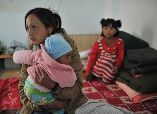 A Myanmar refugee carries a baby at a Chinese border town with Myanmar, Nansan, in Yunnan province, February 16, 2015. (Photo by Reuters/Stringer)