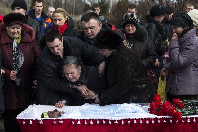 Relatives of a worker Dmitri Aleksandrov, killed by a blast at the Zasyadko coal mine, mourn next to his coffin during a funeral ceremony in Donetsk, March 6, 2015. (Photo by Marko Djurica/Reuters)