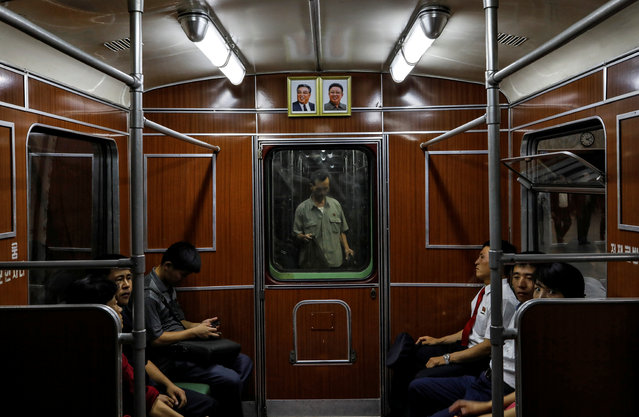 Portraits of late North Korean leaders Kim Il Sung and Kim Jong Il are seen on a train as it leaves a subway station in Pyongyang, North Korea, September 11, 2018. (Photo by Danish Siddiqui/Reuters)