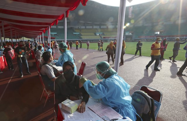 People receive a shot of the Sinovac vaccine for COVID-19 during a vaccination campaign at the Patriot Candrabhaga Stadium in Bekasi on the outskirts of Jakarta, Indonesia, Thursday, July 1, 2021. (Photo by Achmad Ibrahim/AP Photo)