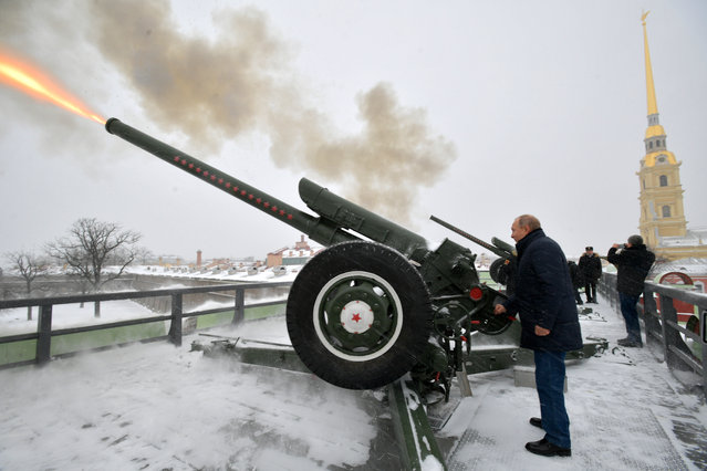 Russian President Vladimir Putin (C) fires a cannon at noon as part of a standing tradition, during his visit to the Peter and Paul Fortress, the original citadel of St. Petersburg, Russia, 07 January 2019. (Photo by Alexei Druzhinin/Sputnik/Kremlin Pool/EPA/EFE)
