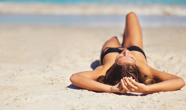 Shot of a young woman lying on the beach. (Photo by Getty Images/Peopleimages)