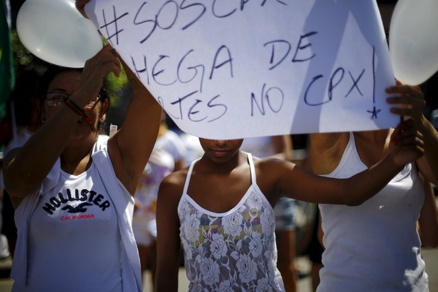 """Residents hold a banner during a protest demanding peace in the Alemao slums complex in Rio de Janeiro April 4, 2015. The residents are protesting against violence in the region and the recent deaths of innocent people during shootouts between policemen and drug dealers, local media reported. The banner reads """"Enough of deaths in CPX (Alemao slums complex)"""". (Photo by Ricardo Moraes/Reuters)"""