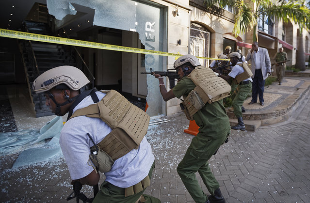 Security forces point their weapons through a shattered door behind which an unexploded grenade lies, at a hotel complex in Nairobi, Kenya, Tuesday, January 15, 2019. Terrorists attacked an upscale hotel complex in Kenya's capital Tuesday, sending people fleeing in panic as explosions and heavy gunfire reverberated through the neighborhood. (Photo by Ben Curtis/AP Photo)