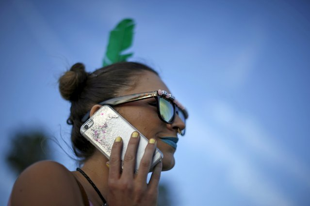 A woman talks on her iPhone as she walks through the Coachella Valley Music and Arts Festival in Indio, California April 10, 2015. (Photo by Lucy Nicholson/Reuters)