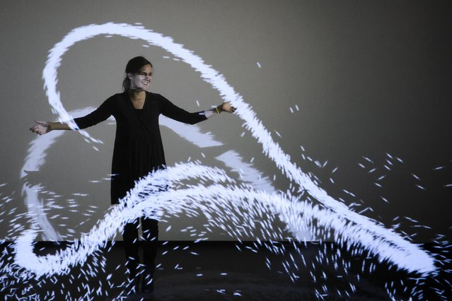 """French artist Claire Bardainne poses in the light installation """"XYZT, Les paysages abstraits"""" (Abstract landscapes) during the press preview for the exhibition """"Danse avec les etoiles"""" (Dance with the stars) in Yverdon-les-Bains, Switzerland, Wednesday, February 17, 2016. (Photo by Jean-Christophe Bott/Keystone via AP Photo)"""