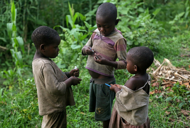 Children hold used syringes, which they found discarded near Kagorwa Pygmy camp on Idjwi island in the Democratic Republic of Congo, November 22, 2016. (Photo by Therese Di Campo/Reuters)