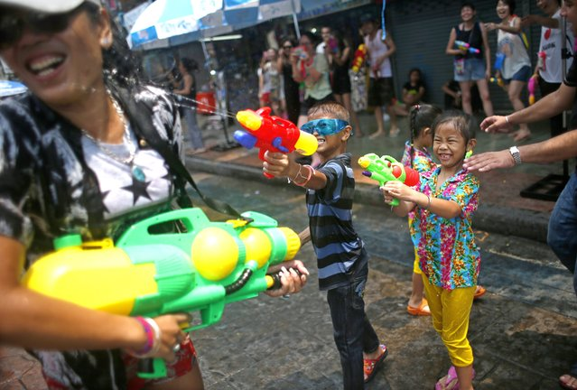 Thai children join the street fun and spray a woman with water from giant water pistols at the popular tourist strip Khao San road on the first day of the water festival Songkran celebrations, the Thai traditional New Year, in Bangkok, Thailand, 12 April 2015. (Photo by Fazry Ismail/EPA)
