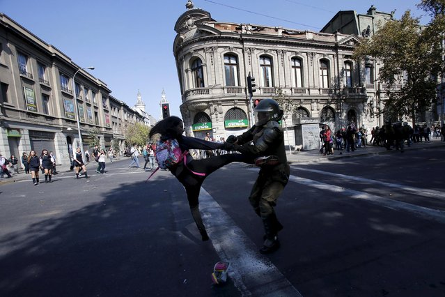 A protester clashes with a riot policeman during a demonstration against the government to demand changes in the education system at Santiago, April 16, 2015. (Photo by Carlos Vera/Reuters)