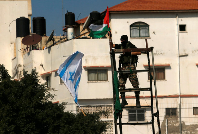 A member of Palestinian National Security Forces loyal to Hamas hangs a Palestinian flag after removing an Israeli flag from a mock Israeli army post as part of a drill during a graduation ceremony, in Gaza City January 22, 2017. (Photo by Suhaib Salem/Reuters)