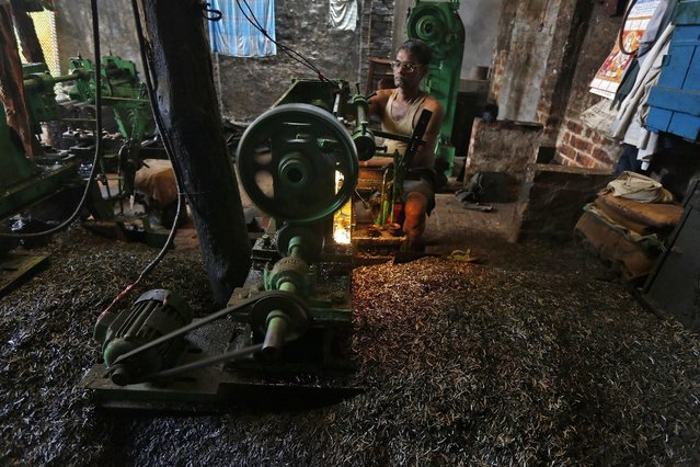 An employee operates a lathe machine as he makes spare parts of crops threshing machines inside a manufacturing unit in Kolkata, India, February 29, 2016. (Photo by Rupak De Chowdhuri/Reuters)