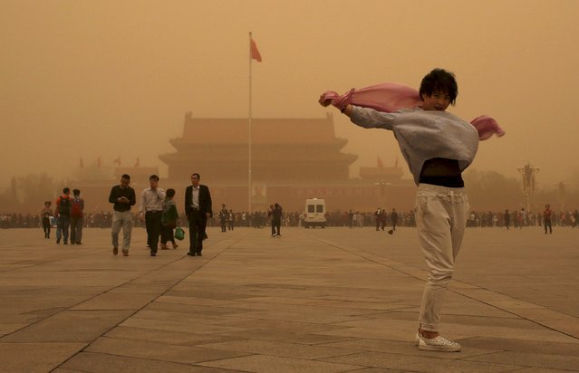 A tourist gestures as she poses for a photograph at Tiananmen Square during a sandstorm in Beijing, April 15, 2015. A sandstorm swept through China's northern regions on Wednesday, shrouding cities in dust and slowing down road traffic. The skyline in Beijing turned orange in the afternoon due to the sandy weather, with vehicles turning on fog lights for safety and many pedestrians wearing masks to protect themselves from the dust. (Photo by Reuters/China Daily)