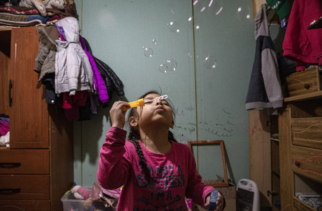 Kehity Collantes blows soap bubbles before going to bed in her home where she lives with her father and aunt in Santiago, Chile, Monday, August 17, 2020, two months after her mother Silvia Cano died of COVID-19. Kehity's mother was hospitalized with pneumonia in May when Chile was going through some of the worst days of its pandemic with around 4,000 new cases reported daily. (Photo by Esteban Felix/AP Photo)