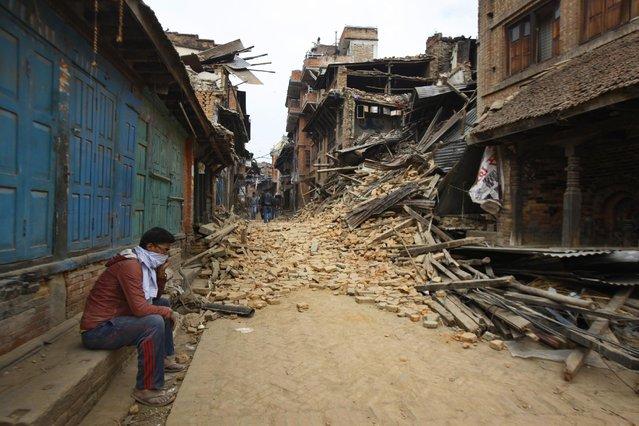 A Nepalese man mourns as he sits near the debris after an earthquake in Bhaktapur near Kathmandu, Nepal, Sunday, April 26, 2015. (Photo by Niranjan Shrestha/AP Photo)