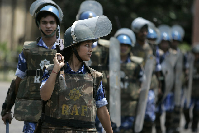 Kakali Mandal, woman personnel of the Rapid Action Force (RAF), marches along with male counterparts at a police training school in Kolkata April 15, 2007. (Photo by Parth Sanyal/Reuters)