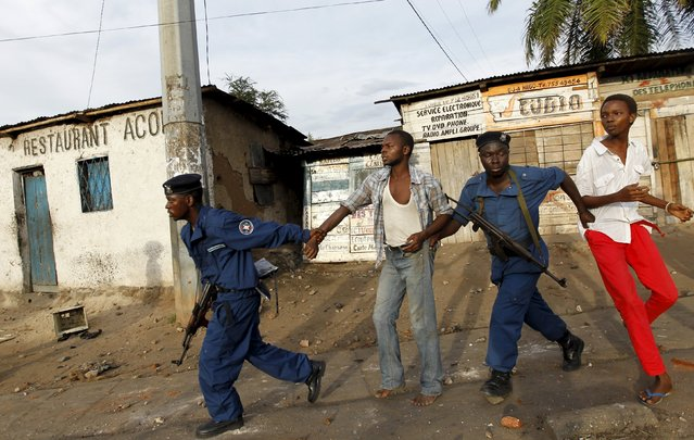 Riot police detain residents participating in street protests against the decision made by Burundi's ruling National Council for the Defence of Democracy-Forces for the Defence of Democracy (CNDD-FDD) party to allow President Pierre Nkurunziza to run for a third five-year term in office, in the capital Bujumbura April 26, 2015. (Photo by Thomas Mukoya/Reuters)