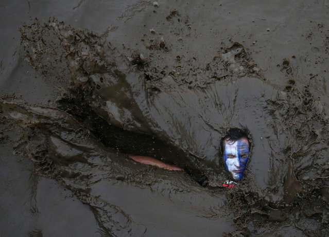 A competitor falls in mud during the Tough Guy event in Perton, Britain, 29 January 2017. The annual event which started in 1987 raises money for charity and challenges thousands of international competitors with a cross country run followed by an assault course consisting of 20 obstacles including water, fire and tunnels. (Photo by Nigel Roddis/EPA)