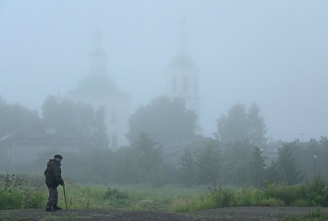 A man walks near a church on a foggy morning in the town of Tara in Omsk Region, Russia on July 18, 2021. (Photo by Alexey Malgavko/Reuters)