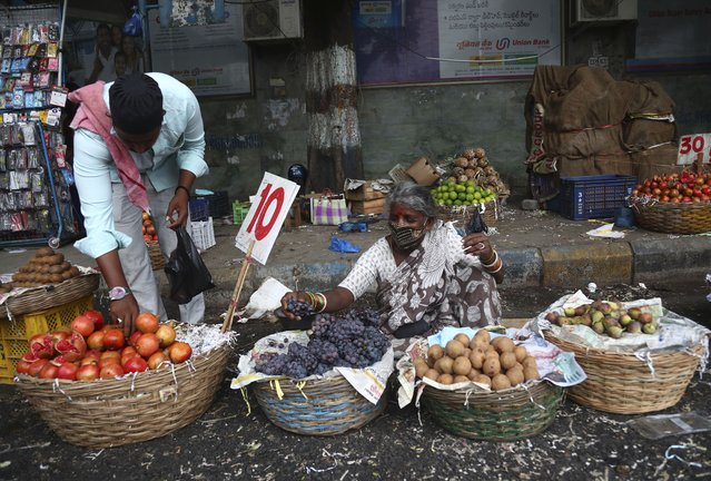 A fruit vendor waits for customers in Hyderabad, India, Friday, June 11, 2021. India's economy was on the cusp of recovery from the first pandemic shock when a new wave of infections swept the country, infecting millions, killing hundreds of thousands and forcing many people to stay home. Cases are now tapering off, but prospects for many Indians are drastically worse as salaried jobs vanish, incomes shrink and inequality is rising. (Photo by Mahesh Kumar A./AP Photo)