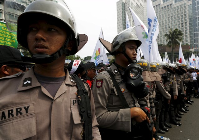 Policemen stand guard as workers hold a May Day rally at a business district in Jakarta, Indonesia, May 1, 2015. (Photo by Reuters/Beawiharta)