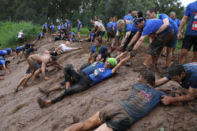 Participants help each other through a muddy obstacle course during the Tel Aviv Mud Run race in the Yarkon Park, in Tel Aviv, Israel, 29 March 2019. (Photo by Abir Sultan/EPA/EFE)