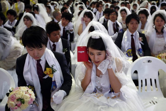 A bride talks on the phone during a mass wedding ceremony of the Unification Church at Cheongshim Peace World Centre in Gapyeong, about 60 km (37 miles) northeast of Seoul February 12, 2014. The Unification Church founded by evangelist reverend Moon Sun-myung in Seoul in 1954, performed its first mass wedding in 1961 with 33 couples. Approximately 2,500 couples attended the mass wedding on Wednesday. (Photo by Kim Hong-Ji/Reuters)
