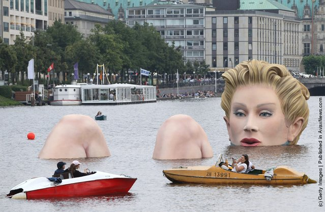 People in boats approach Die Badende (The Bather), a giant sculpture showing a woman's head and knees as if she were resting in the Binnenalster lake in Hamburg, Germany