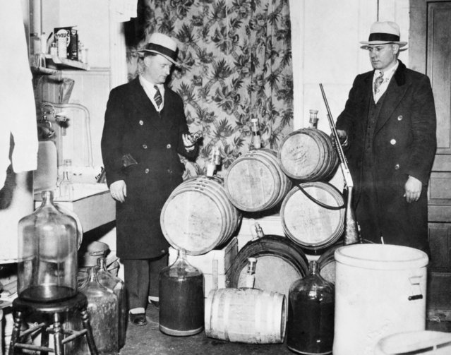Police officers look over distilling equipment and guns confiscated during a Prohibition raid, Chicago, ca.1920s. (Photo by Chicago History Museum/Getty Images)