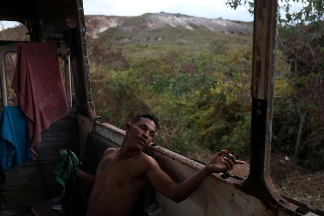 Venezuelan Hildemaro Ortiz relaxes inside of an abandoned bus in the border city of Pacaraima, Brazil on April 13, 2019. Ten destitute Venezuelan migrants who fled their country's crisis did not get far when they crossed into Brazil: they have been living for three months on an abandoned bus just across the border. (Photo by Pilar Olivares/Reuters)