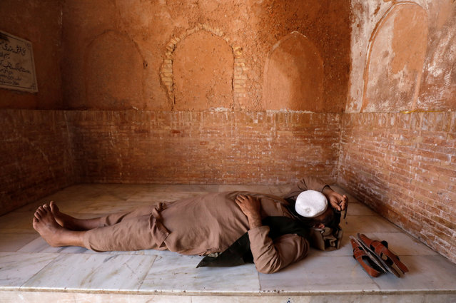A man with a cap on his face sleeps on a floor at the Mahabat Khan Mosque in Peshawar, Pakistan on March 4, 2019. (Photo by Fayaz Aziz/Reuters)