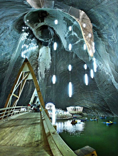 Tourists taking boat rides in the underground lake located within the salt mine museum in Turda, Romania. (Photo by Sorin Toma/Hepta/Barcroft Media)
