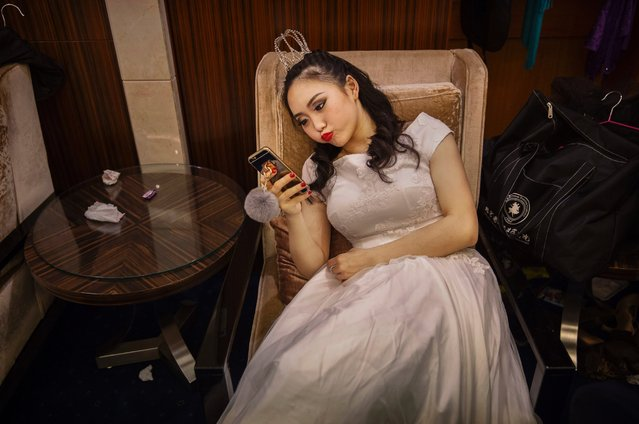 A debutante from a local academy looks at her mobile phone as she waits to take part in the Vienna Ball at the Kempinski Hotel, March 19, 2016, in Beijing. (Photo by Kevin Frayer/Getty Images)