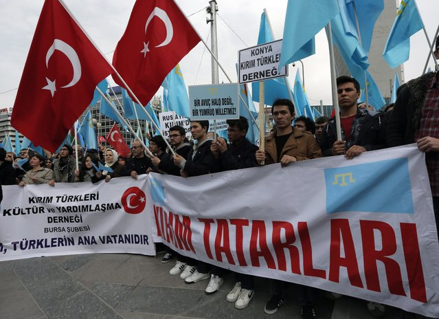 "Turks of Crimean Tatar origin wave Turkish and Crimean flags as they demonstrate to protest against Russia's military intervention in Crimea, Ukraine, in Ankara, Turkey, Sunday, March 2, 2014. The banner reads: ""Crimean Tatars"". (Photo by Burhan Ozbilici/AP Photo)"