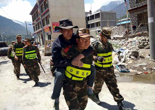 A rescuer carries a man on his back as authorities carry out rescue operations after a fresh 7.3-magnitude earthquake hit Nepal, in Gyirong county, Tibet Autonomous Region, China, May 12, 2015. (Photo by Reuters/Stringer)