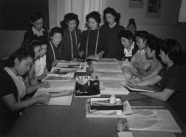 Mrs. Ryie Yoshizawa and a class of female students sit at a table looking at fashion magazines and patterns. The students are: Satoko Oka, Chizuko Karnii, Takako Nakanishi, Kikiyo Yamasuchi, Masako Kimochita, Mitsugo Fugi, Mie Mio, Chiye Kawase, and Miyeko Hoshozike, at the Manzanar War Relocation Center in California, in this 1943 handout photo. (Photo by Courtesy Ansel Adams/Library of Congress, Prints and Photographs Division/Reuters)