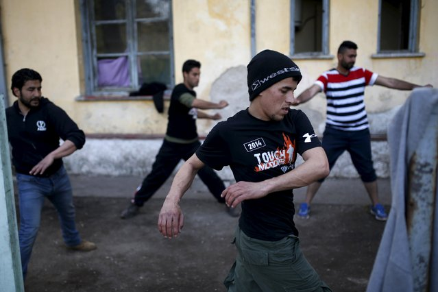Migrants and refugees exercise at a makeshift camp at the Greek-Macedonian border near the village of Idomeni, Greece, March 30, 2016. (Photo by Marko Djurica/Reuters)