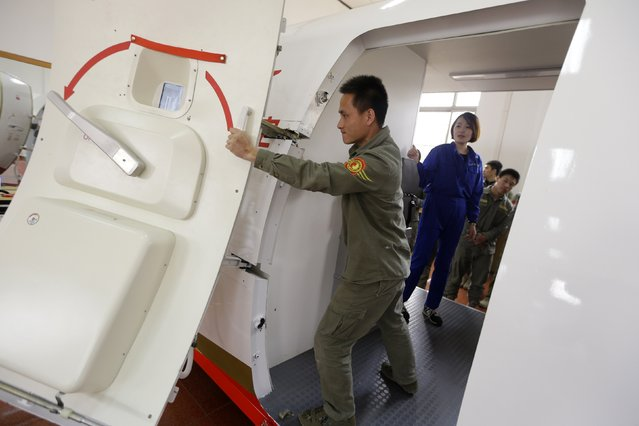 A trainee of the Tianjiao Special Guard/Security Consultant bodyguard training camp opens a cabin door inside a scale model of a passenger jet during an emergency evacuation course at a flight attendant training centre on the outskirts of Beijing, March 18, 2014. (Photo by Jason Lee/Reuters)