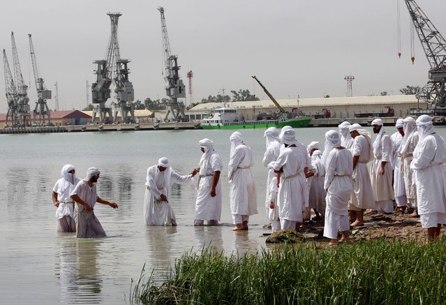 Members of the Sabean Mandaeans, a pre-Christian sect that follows the teachings of John the Baptist,  take part in a bathing ritual during the Baptism Festival, on the banks of the Shatt al-Arab waterway in Basra, 340 miles (550 kilometers) southeast of Baghdad, Iraq, Wednesday, May 20, 2015. (Photo by Nabil al-Jurani/AP Photo)