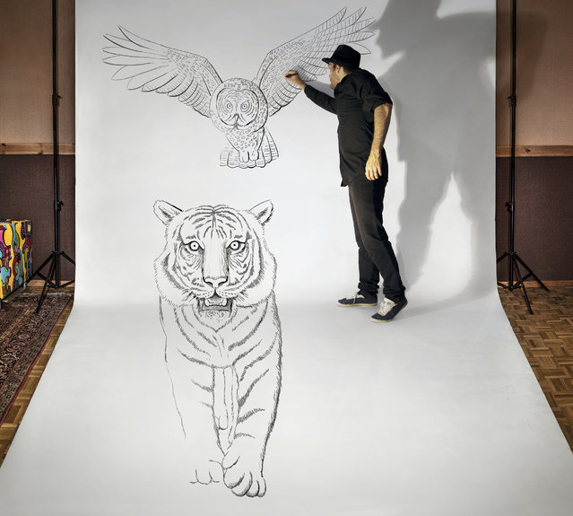 "Visual artist Ben Heine at work in his studio while he creates one of his ""anamorphic illusions"" in Rochefort, Belgium. (Photo by Ben Heine/Barcroft Media)"