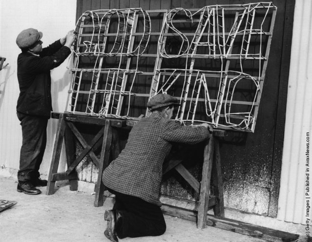 1935: Two men making a fireworks set piece with the slogan 'God Save The King' for despatch abroad, for the Silver Jubilee celebrations of King George V