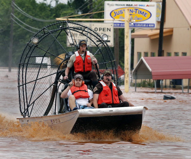 Highway patrolmen rescue Justin Nimmo, left, from his business, Just-In-Time, after flooding caused by rising water from Saturday night's storms trapped him in the store on Sunday, May 24, 2015 in Purcell, Okla. (Photo by Steve Sisney/The Oklahoman via AP Photo)