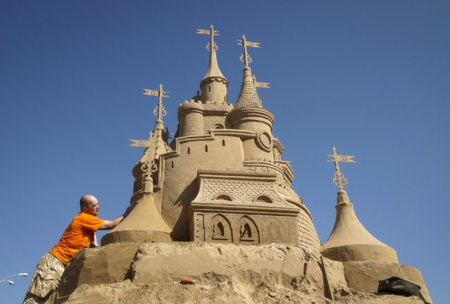 """Dmitry Glebezdov of Russia works on his creation during the Sand Sculpture Festival """"Sand Fantasy"""" in Almaty, Kazakhstan, April 15, 2016. (Photo by Shamil Zhumatov/Reuters)"""