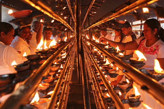 Sri Lankan Buddhist devotees light oil lamps as they mark Poya day or Full Moon Day at a temple on November 22, 2018 in Colombo, Sri Lanka. Buddhists, who make up 60 percent of the country's population, dress in white and perform rituals on Full Moon Day, a public holiday in Sri Lanka. (Photo by Buddhika Weerasinghe/Getty Images)