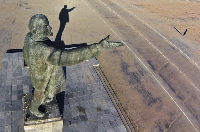 In this aerial photo a woman walks past a statue of Soviet Union founder Vladimir Lenin at the Russian leased Baikonur cosmodrome, in  Kazakhstan, Thursday, March 27, 2014. Baikonur is the world's first and largest operational space launch facility. (Photo by Dmitry Lovetsky/AP Photo)