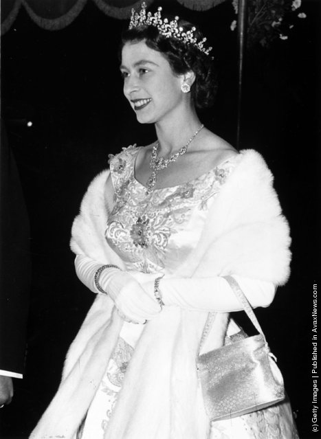 1955: A regally adorned Queen Elizabeth II arriving at the Royal Performance of the film 'To Catch A Thief' at the Odeon Cinema, Leicester Square