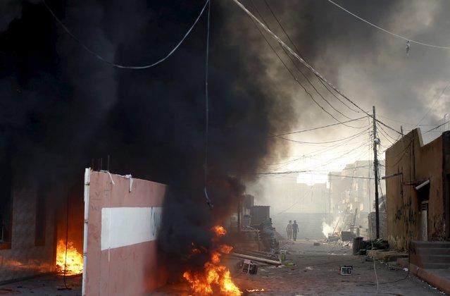 Kurdish men walk near a burning house of a Shi'ite militiaman during clashes in Tuz Khurmato, Iraq, April 24, 2016. (Photo by Goran Tomasevic/Reuters)