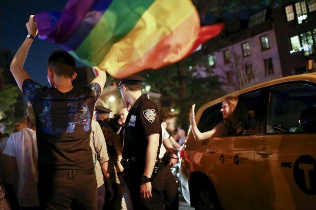 A woman tries to shake hands with a NYPD officer trying to re-open the street for traffic as people celebrate outside the Stonewall Inn, late in the night in the Greenwich Village neighborhood of New York June 26, 2015. (Photo by Eduardo Munoz/Reuters)